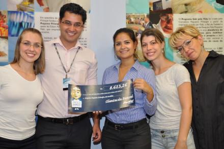 Renata Iório, gerente dos Novos Projetos,recebe  da equipe Panvel o cheque simbólico.