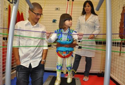 Alex com paciente e fisioterapeuta na sala de fisioterapia que recebe seu nome