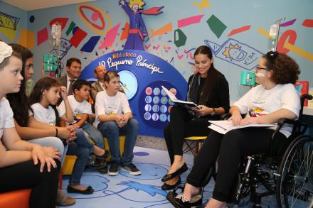 """A top model Adriana Lima faz uma leitura de """"O Pequeno Príncipe"""" para pacientes no novo espaço cultural do hospital."""